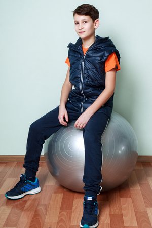 fitball: Boy teenager sitting on fitball. Fitness child in sportswear on a white blue background.