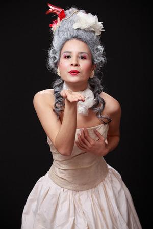 air kiss: Baroque stilisation. Portrait of a young tender woman in crinoline dress  sending air kiss, playful expression, dark background