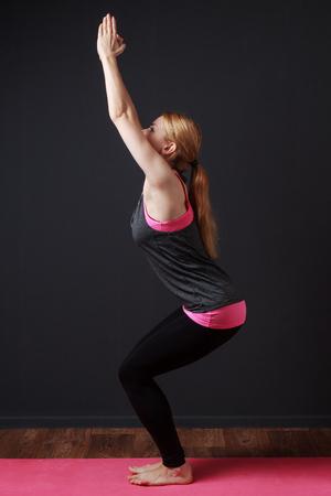 moksha: Chair pose. Yoga. Young blonde woman doing yoga exercise Stock Photo