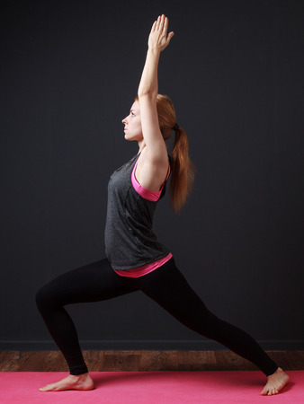 prana: Yoga. Young blonde woman staying in warrior pose ( hands up) Stock Photo