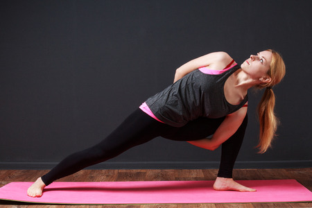 prana: Yoga pose. Eagle twist. Young blonde woman doing yoga exercise Stock Photo