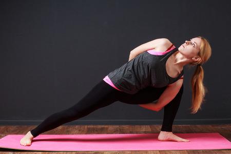 moksha: Yoga pose. Eagle twist. Young blonde woman doing yoga exercise Stock Photo