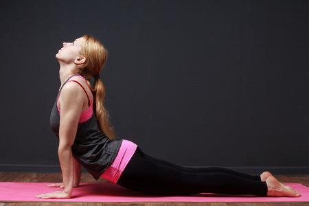 disciplina: ejercicios de yoga. Mujer rubia joven en actitud de la cobra