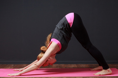 prana: Yoga exersices. Young blonde woman staying in downward dog pose