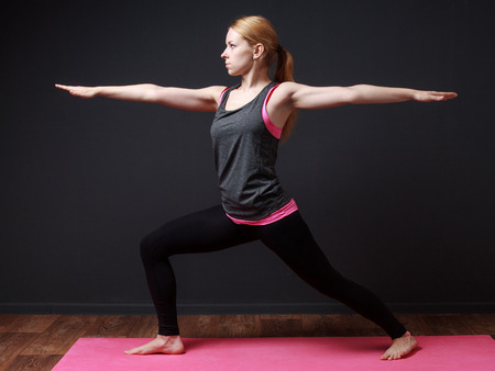 prana: Yoga. Young blonde woman staying in warrior pose Stock Photo