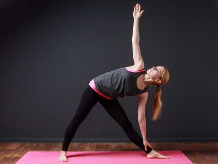 prana: Yoga. Young blonde woman staying triangle pose