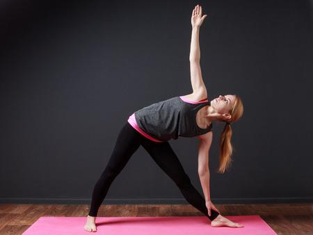 moksha: Yoga. Young blonde woman staying triangle pose