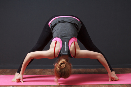 prana: Exerxicises for the hips. Yoga. Deep bend with straddled legs. Woman doing workout. Stock Photo