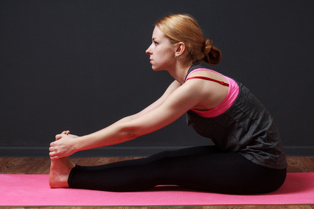 prana: Seated forward fold. Yoga.Young blonde woman doing yoga exercise