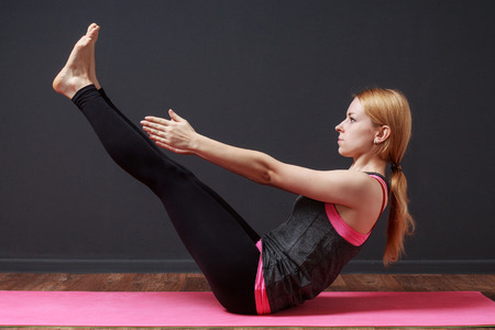 prana: Paripurna Navasana. Full Boat Pose. Young blonde woman doing yoga exercise