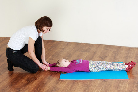 Physiotherapy for children. Trainer is doing stretching with a little girl lying on a mat Stock Photo