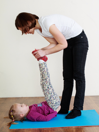 Physiotherapy for children. Trainer is helping little gitl to do an exercise Reklamní fotografie