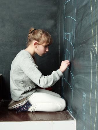 Children. Little girl is drawing on a blackboard, profile view