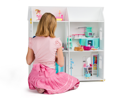 dollhouse: Childhood. Little girl is playing with the dollhouse full of dalls and furniture, view from the back, isolated on white background
