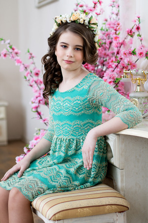 dinky: Portrait of a cute little girl in a flower wreath and a blue dress