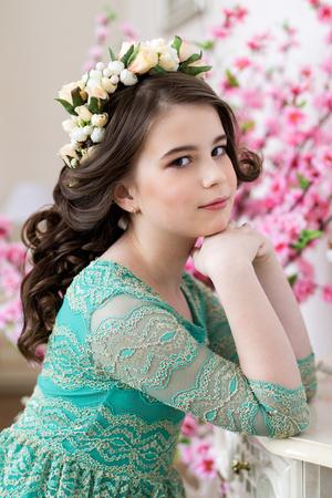 Close up portrait of a cute little girl in a flower wreath
