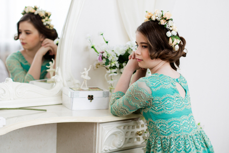 dinky: Little pensive girl in flower  wreath is sitting at the dressing table in front of a mirror
