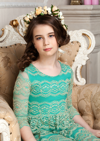 dinky: Portrait of a beautiful little girl in the flower wreath sitting on the chair, smiling, luurious interior