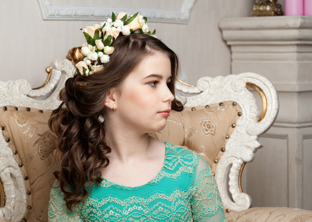 dinky: Portrait of a cute little girl in the flower wreath sitting on the chair, smiling, profile view