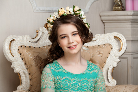dinky: Portrait of a smiling little girl in the flower wreath sitting on the chair, smiling, luurious interior