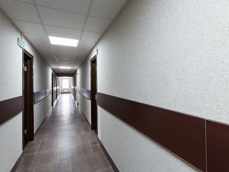 hospital interior: Interior - long corridor with doors and window light at the end