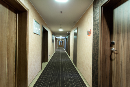 The interior of this hotel - a long corridor with several doors
