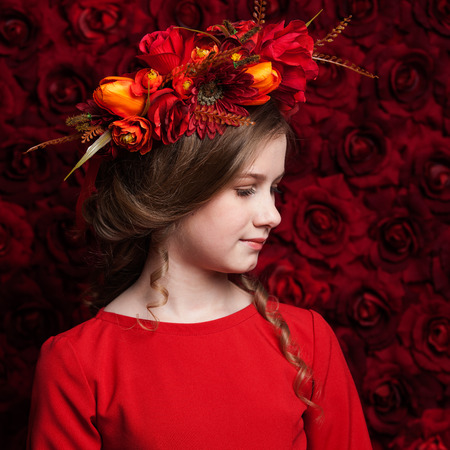 dapper: Close up portrait of a little cute girl in a flower wreath, red roses background