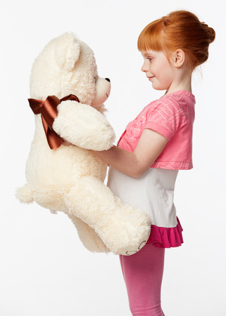 children clothing: Portrait of a smiling redheaded girl in a pink shirt hugging the bear toy, isolated on white background, profile view Stock Photo