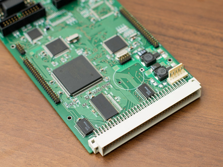 echnology: Green circuit board with a large plug on a brown table