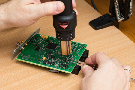 soldered: Mans hand holds the soldering station. Engineer chip is soldered to the board.