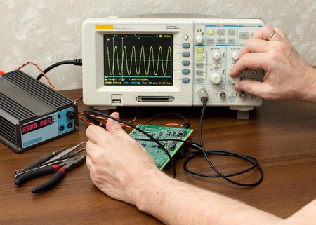 oscilloscope: Workplace engineer. Mans hand adjusts the amplitude of the sine wave on an oscilloscope.