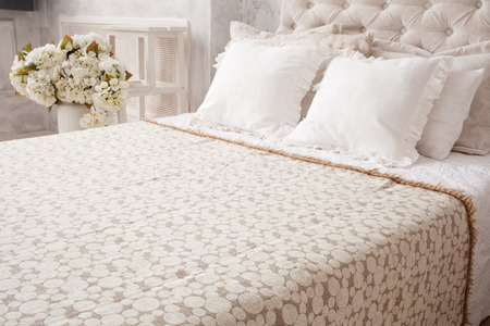 bedspread: Interior. Bedroom. Close up white bed with  bedspread and pillows, flowers behind