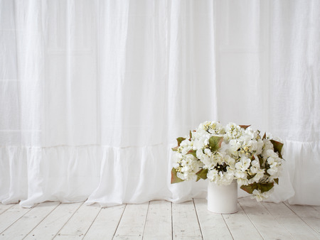 Interior. Window design. White curtains, vase with flowers on the wooden floor