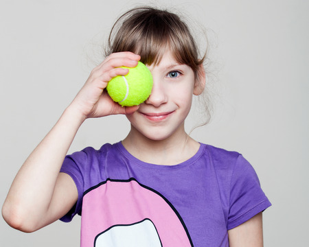 eye ball: Children. Close up portrait of a cute girl holding a tennis ball at the eye, smiling, gray background