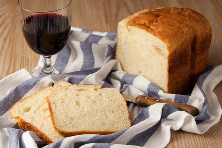 life loaf: Food. Still life. A glass of red wine, loaf of bread  and a knife on a table-napkin