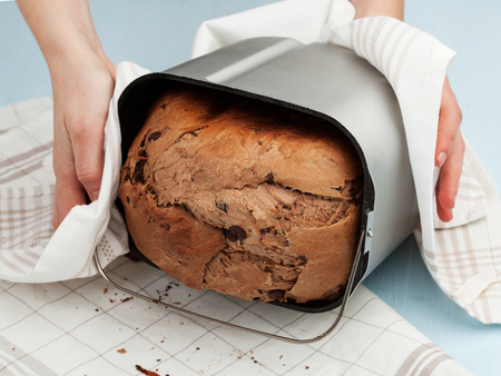 life loaf: Food. Womans hands taking off bread from the breadmaker