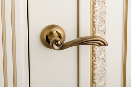 gilded: Interior. Close up an elegant gilded doors handle, an element of the doors molding