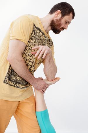 somatic: Massage and rehabilitation. Man  manipulates on womans leg.