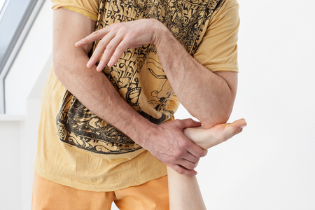 somatic: Thai massage session. Man presses on womans leg by the elbow