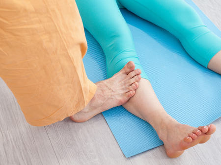somatic: Thai massage session. Man presses on womans leg by the foot