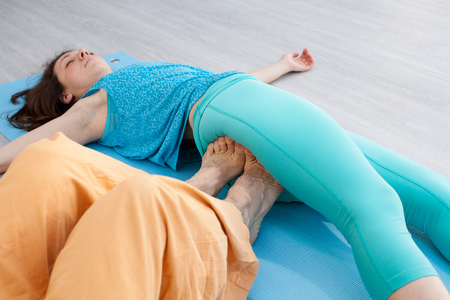 somatic: Thai massage session. Man presses on womans buttock by the feet