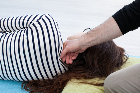 somatic: Reflexology. Mans hand manipulates on the womans neck by the knuckles, woman lays on the mat