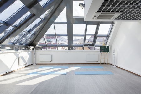 floor mats: A place for sports training in yoga and fitness. Several mats lie on the floor. The interior gym with a large window in the ceiling and patches of sunlight on the white wall. Stock Photo