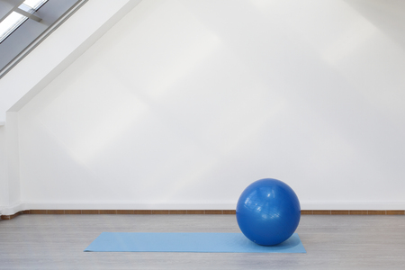 Place for fitness exercises. Fitbol mat  lies on the floor. The room is flooded with sunlight from the window, the glare on the white wall.