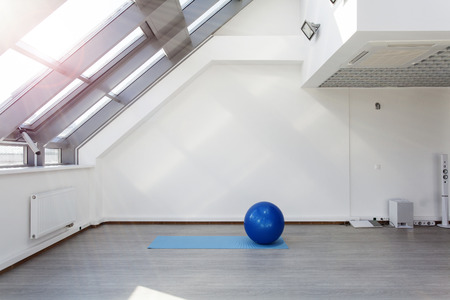 audio: Gym for fitness exercises. Fitbol and mat  lie on the floor. The room is flooded with sunlight from the window, the glare on the white wall. Audio system with speakers in the background.