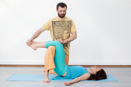 somatic: Pair exercises. Massage. Man performing thai massage, srtetching womans legs, presses on her foot