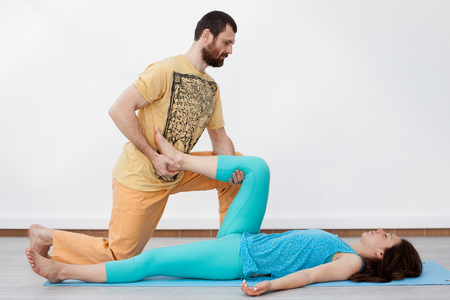 somatic: Pair exercises. Massage. Man performing thai massage, strtetching womans leg, presses on her heel