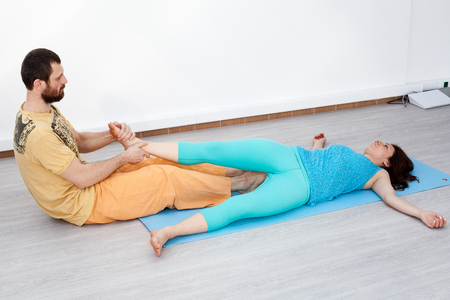 somatic: Pair exercises. Stretching. Man performing thai massage, srtetching womans legs, woman is laying on the mat relaxing