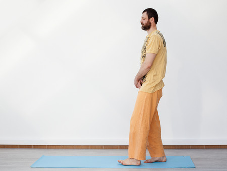 meditative: Yoga. Meditative walking. Young bearded man performing meditative walking on the mat