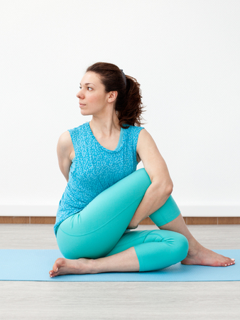 torsion: Yoga. Fitness. Stretching. Young woman is performing twist on the mat, white background